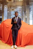 African car salesman using smart phone in showroom. Happy african car salesman using smart phone in showroom royalty free stock image