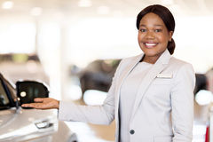 African car saleswoman. Beautiful african car saleswoman presenting new vehicles stock image