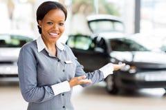 African car saleswoman presenting. Friendly african car saleswoman presenting new vehicles Stock Photos