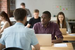 African and caucasian entrepreneurs discussing project in co-wor. African american and caucasian entrepreneurs discussing project at meeting in co-working space Stock Image