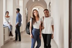 African and Caucasian female students resting on corridor. royalty free stock photography