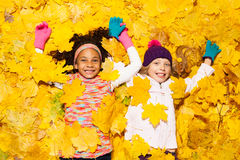 African and Caucasian girl covered in maple leaves Royalty Free Stock Photos