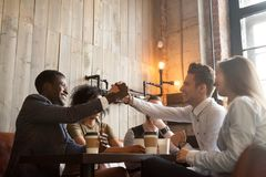African and caucasian men handshaking at coffeehouse meeting wit. African american and caucasian men shaking hands at coffeehouse meeting with diverse friends Stock Images