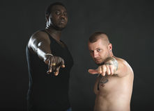 African and caucasian pointing fingers at camera. royalty free stock images