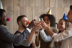 African and caucasian young friends clinking glasses celebrating. Party together, diverse people in funny hats laughing having fun toasting with champagne Stock Image