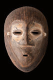 African mask. An African ceremonial mask carved in wood with white pigment signifying anti-witchcraft powers, isolated on black stock photography