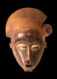 African mask. An African ceremonial mask in the form of a female figure carved in wood isolated on black stock photo