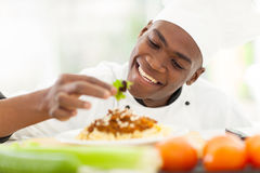 African chef decorating. Cheerful african chef decorating spaghetti Royalty Free Stock Photos