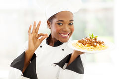 African chef delicious. Attractive young african chef with delicious pasta dish Stock Images