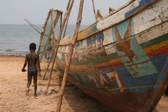 African child. Young child on a beach in west -africa, with fishing boat Stock Image