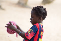 African child. Beach, Abidjan, Côte d'Ivoire-August 29, 2015: A little girl makes a cushion with a piece of fabric that will serve her to carry her goods Royalty Free Stock Photos