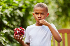 African child eats cherries Royalty Free Stock Photo