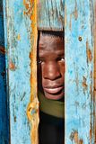 African child portrait. African child hiding behind a door in the village, Botswana Royalty Free Stock Image