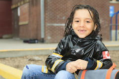 African child in the playground of a shool. An african child in the playground of a shool with raincoat Royalty Free Stock Photos