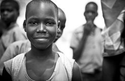 African child in Uganda posing for the camera. Happy African child in Uganda posing for the camera amongst a group of other children in the background stock photo