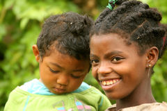 African childcare. Young girl taking care of her younger brother royalty free stock image