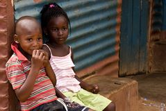 African children. Two african children sitting at the door of their township shack. Poverty is very common in South African townships and all over Africa royalty free stock image