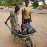 African children. Take fun with a wheelbarrow. The photo is taken in Ghana - Africa Stock Photo