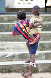African children. Abidjan, Ivory coast-August 29, 2015: A young girl carrying a baby, left foot attached by a piece of cloth, goes up the stairs Royalty Free Stock Images