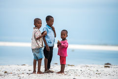 African children. Children in Africa face poor life conditions, however they are curious and joyful. Image of siblings on the beach of Zanzibar Island right Stock Image