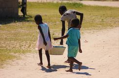 African children carry water back home. Young African children carry water from the village water tap back home to do their washing stock photo