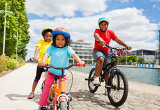 African children cycling along a river embankment. Happy age-diverse African children in safety helmets cycling along a river embankment at summer day Stock Image