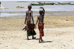 African children. Of the Dasanech or Galeb ethnic group are walking along the shore of the Turkana lake, Ethiopia, bringing the bottles of water stock photos