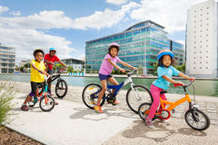 African children enjoying cycling together in town. Side view portrait of age-diverse African children cycling together on a river embankment in summer Royalty Free Stock Photography