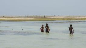 African children playing in the ocean. Near seaweed farm Zanzibar, Tanzania - February 2019 royalty free stock photo