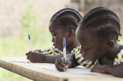 African Children at School Doing Homework. African ethnicity stu. Dents writing their essay in an African school. They`re holding blue pens to write down their stock photography