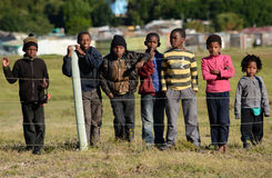 African children in township. A group of African children of the Seaview informal settlement in Port Elizabeth, South Africa, standing behind a fence and staring Royalty Free Stock Image