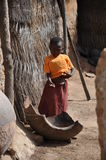African children in a village. An African children with a sad look near a big broken container.  These containers are used to cook the beer made with millet Stock Photography