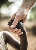 African childs hand holding a white adults hand Stock Image