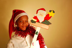 African christmas woman. Studio portrait of a young African black woman with smiling facial expression dressed as Santa Claus and holding a christmas sign Royalty Free Stock Photos