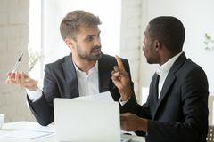 African client having claims about document disagreeing with cau. African black client having claims about business document disagreeing with caucasian partner Stock Photo