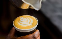 African Coffee Barista pouring a leaf shape with milk foam. In a take away cup stock photo