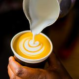 African Coffee Barista pouring a leaf shape with milk foam royalty free stock image