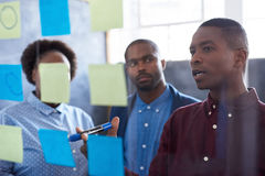 African colleagues strategizing with sticky notes on a glass wall. Three casually dressed African work colleagues brainstorming on a glass wall with sticky notes stock photos