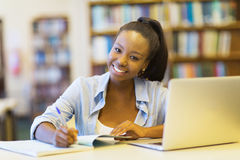 African college student studying. Beautiful african college student studying a book in library Stock Photography