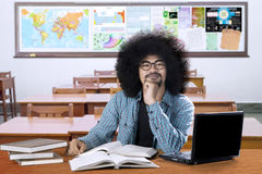 African college student thinking idea. African college student sitting in the classroom while thinking idea with laptop and books on the table Stock Image