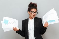 African confused business woman with diagramas documents. Image of young african confused business woman standing over grey wall with diagramas documents Royalty Free Stock Image