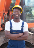 African construction worker with crossed arms and red excavator Royalty Free Stock Photos