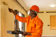 African construction worker. Professional african construction worker painting the wall Royalty Free Stock Photo