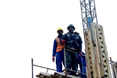 African Construction Workers. Three african men on a job site wearing helmets of a building going up in Muizenberg, Cape Town, South Africa stock photos