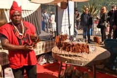African cook preparing grilled meat skewers at street food festi Stock Image