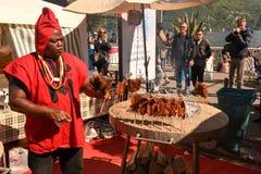African cook preparing grilled meat skewers at street food festi Stock Images