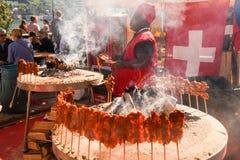 African cook preparing grilled meat skewers at street food festi Royalty Free Stock Photo