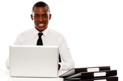 African corporate male manager at work desk. Using laptop and looking at camera Stock Photo