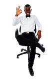African corporate man showing okay gesture. Successful african corporate man sitting on chair and showing okay gesture to camera Stock Photo