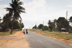 African couple carrying goods at the side of the road in Tofo Royalty Free Stock Image